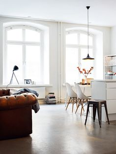 Lovely casual space with great light, white furnishings and leather tufted sofa