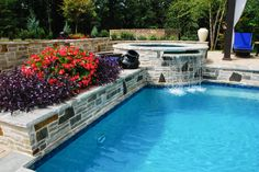 A beautiful spill-over from spa by Peach State Pool Builders next to beautiful stone work placement for some gorgeous landscape.