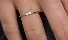 Single Baguette Diamond Ring : A single baguette cut diamond lies across a slender gold band perfect for stacking with other rings. a gift that is truly flawless for your loved one. Features : • Gold KT: 14K • Ring Size: 4-14 • Custom Gold Color: Rose Gold, Yellow Gold, White Gold •