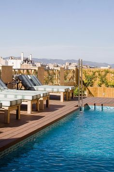 The narrow rooftop pool is bordered by cushioned sun loungers. Cotton House Hotel, Autograph Collection (Barcelona, Spain) - Jetsetter