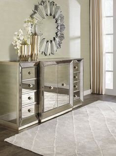 Omni Mirrored Buffet - combines glamour with purpose. The clean lines of the cases are outlined in a hand- applied silver leaf and silver beaded trim while the drawers are accented with a brushed silver hardware. Mirrored.