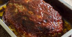 Brown gravy meatloaf sits on a plate and is surrounded by yummy sides of sweet peas, mashed potatoes, and salad. Smothered meatloaf.