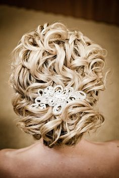 maybe a hairstyle to consider? But less stiff looking, maybe with soft curls and a piece or two out in the front