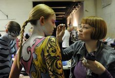 Katelyn Simkins , right, works on the eyebrows of Rachel Fisher as the Denver Fashion Weekend held it's day two fashion show which featured body painting at the EXDO Event Center in Denver on Friday, March 2, 2012. The body painting was carousel inspired. Cyrus McCrimmon, The Denver Post