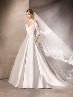 La Sposa HALAZGO Elegant ptincess dress in a Mikado silk skirt. The bodice merges into the skirt and are both made of lace Tulle and Gemstones thar create a feminine sweetheart neckline, under an envelope neckline in crystal Tulle.