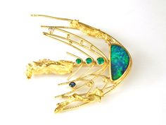 Another of my comet series of pins.  Boulder opal, emeralds, sapphire and diamond.  18k and 22k gold.