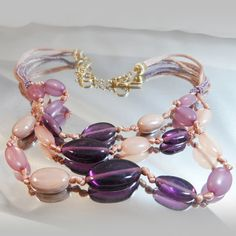 This #vintage purple glass bead necklace is absolutely gorgeous!  It features a three strand necklace with a dropped down focal point filled with four shades of purple and l... #ecochic #etsy #jewelry #jewellery