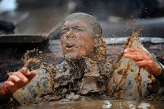 """A competitor in fancy dress emerges from muddy water during the Tough Guy Challenge endurance race in Perton, England, on January 29, 2012. Every year thousands of people run the 8 mile assault course which involves freezing temperatures, fire and ice. First staged in 1986, it has been widely described as """"the toughest race in the world"""", with up to one-third of the starters failing to finish in a typical year. (Michael Regan/Getty Images)"""