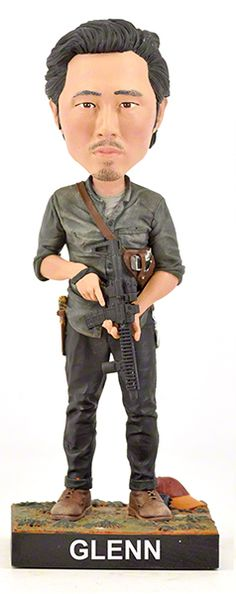 Glenn bobblehead from the hit TV show THE WALKING DEAD. Features Glenn holding his AR-15, with his iconic baseball cap and walkie-talkie at his feet.