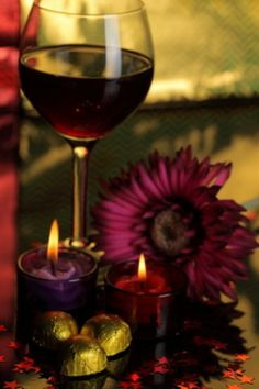 Red wine by candles and a flower