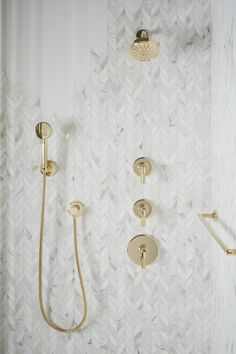 A unique geometric pattern and detailed artisan design, bring beauty to the bathroom for years to co… Chevron Bathroom, Chevron Tile, White Bathroom Tiles, Gold Bathroom, Bathroom Ideas, Bathroom Colors, Shower Tile Patterns, Gold Faucet, Gold Shower
