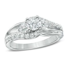 Polished and diamond-lined ribbons create the ring's shank, wrapping the center stones in a sparkling embrace.