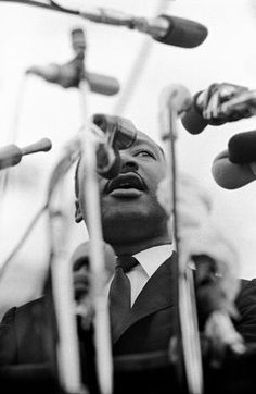 Dr. Martin Luther King, Jr. seen through sea of microphones, speaking before crowd of 25,000 civil rights marchers, in front of Montgomery, Alabama state capital building.