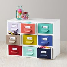 """""""Color Reference Drawers"""" -- These rather adorable card-catalog-inspired drawers are out of stock at the click-through right now, but expected """"in early August"""" (2015). All white/grey unit, """"Dewey Decimal Drawers"""" (no longer available) can be seen here: http://www.landofnod.com/grey-decimal-drawers/s202220"""