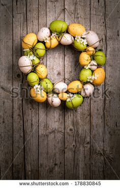 Easter wreath from eggs and spring flowers, appended at wood wall. by eZeePics Studio, via Shutterstock