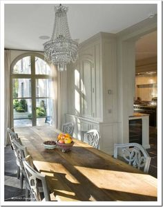 juxtaposition of large scale rustic dining table with formal crystal chandelier. french atmosphere <3