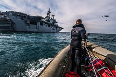 A search and rescue swimmer assigned to the amphibious assault ship USS Boxer (LHD 4) stands watch aboard a 7-meter rigid hull inflatable boat. Boxer is currently conducting operations off the coast of southern California. (U.S. Navy photo by Mass Communication Specialist Seaman Apprentice Veronica Mammina/Released)