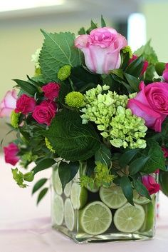 Beautiful green arrangement with a hint of pink. Love the limes in the vase as well!