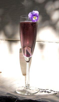 Purple Champagne 1 oz Crème De Violette Liqueur Champagne Violet, pansy, or viola blossom to garnish (optional, but recommended)