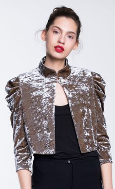 This elegant high collared plush velvet cardigan is detailed with mutton sleeves and fastened with polished metal button. The mid elbow length sleeves and slightly cropped length mean it sits well with short and long dresses or high-waist pants or skirts.