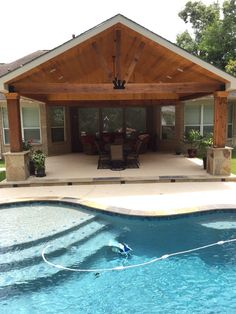 Photo of Backyard Paradise - Magnolia, TX, United States. Gable roof patio cover attached to existing house with cedar beams and posts, flags or column base, and wood stained ceiling