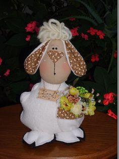 Meiga ovelhinha confeccionada em:  - unifloc,  - enchimento de fibra siliconada,  - feltro, tecido de algodão, lã, flores artificiais, plaquinha de mdf.  - areia.   Valor unitário.   * Pedidos não confirmados em 3 dias serão cancelados.