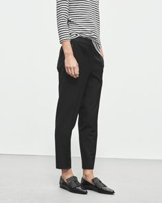 A looser slightly carrot shaped fit with elastic at waist and sewn press creases. Perfectly combines sporty ease with tailored style. Wear with masculine flats for a look that is both relaxed and well dressed.