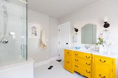 A once cramped and dingy bathroom is now a stunning spa-like space, complete with a clawfoot soaking tub and walk-in shower. A bright yellow cabinet pops against the black and white color scheme.