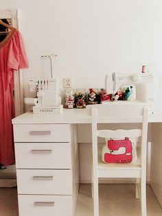 cute little sewing area. i think this person also stores clothes in the same room. great usage of space.