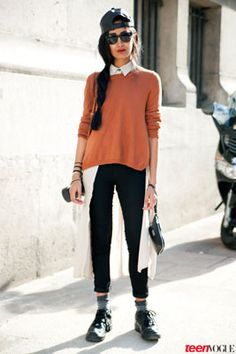 A pumpkin orange sweatshirt adds a pop of autumn color to a white dress layered on top of black pants. Blogger #NadiaSarwar completes the look with a backwards baseball cap and rugged sneakers.