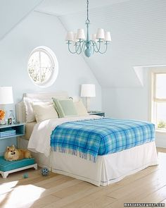 Pop of Color - The key to enlivening a neutral room is to brighten it with several shades of the same color. In a mostly pale room, a plaid blanket makes a strong statement. The chandelier, the wall-mounted bedside tables, and the cushion on the dog bed reiterate the blanket's several shades of blue. Orange poppies add a vivid, albeit temporary, secondary color.
