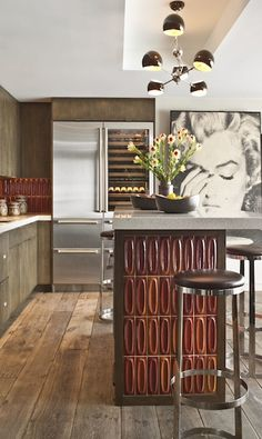 The bold tiles aren't the only statement-making piece in the kitchen. A dramatic artwork depicting a seemingly saddened Marilyn Monroe also creates an arresting focal point.