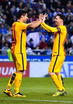 Lionel Messi of FC Barcelona celebrates with his team mate Luis Suarez after scoring his team's sixth goal during the La Liga match between RC...