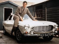"""Sir Roger Moore English star actor is sitting on Volvo P-1800 classic sport car from """"The Angel"""" cryme TV-movie series."""