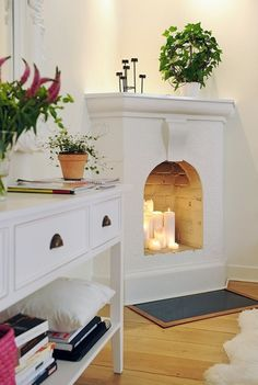 Living room: light large candles in an unused fireplace