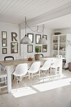 {dining gallery} bright and white eating area backed by a gallery wall.