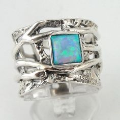 NEW artistic silver Ring from my collection. This ring has a square 5mmx5mm Opal inlaid in very artistic 16mm textured solid silver band.   Avaliable in many other stone. Ask me...   Labeled and stamped 925. This beauty will be sent to you in a gift package. (All stains, if are any, are due to camera). Please feel free to contact us at any matter. Material: Sterling Silver 925 925 Dimensions: width: 16 mm / 0.629 in. Size: 8 (and can be resized at your request) Thank you for looking...