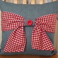 This cushion cover has been handmade from a light blue denim and the beautiful bow has been made from a very cute red and white gingham polycotton. The 'tie' in the middle of the bow is made from denim and is backed with the gingham. To enable the...