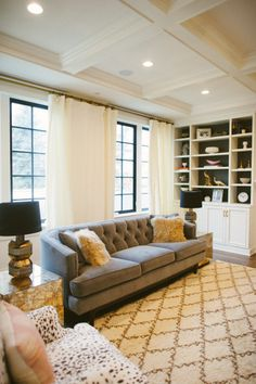 christine dovey asbury living room 6 tufted sofa dweel vintage lamps  mirrored side tables black windows coffered ceiling bookcases