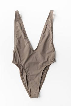 Low V-neck one piece swimsuit in khaki. High leg cut with cheeky bottoms and an open back. Gold accents on adjustable straps. Made and manufactured in the USA at the highest quality standards. We sugg