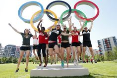 Members of Canada's Olympic basketball team jump for joy in front of the rings at London's Olympic Village on Tuesday JULY 24 2012. AP photo.