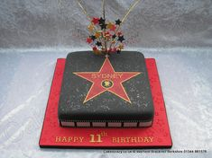 zHollywood Walk Of Fame Cake. Single tier Hollywood walk of fame star cake. The star has a movie icon and a name, the gold edges are hand painted. Finished with a wired topper of red black and gold and red/black wired twirlers and a movie film strip surrounds the cake