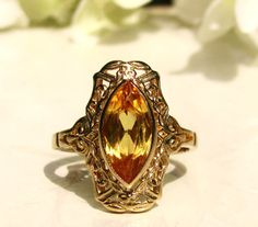 This beautiful vintage yellow sapphire engagement ring is such a stunning and beautiful reproduction imitative of the detailed craftsmanship from the Edwardian/Art Deco era made by the Plainville Stock Co. established in Massachusetts in the late 1800s-present! Possibly one of their original casted rings or one of their beautiful retro reproductions made in later times that is in excellent condition! The ring is a marquise shaped 10K yellow gold filigree ring with a beautifully faceted…