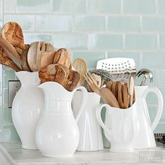Use white pitchers and vases as utensil storage. They look pretty displayed out on the counter. Love this aqua subway tile, too!