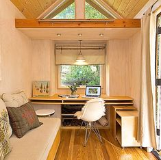 This woman\u0027s self\u002Ddesigned tiny home has a light\u002Dfilled living room that incorporates a great workspace.