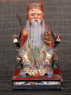 Wooden statue of Tu Di Gong, the Chinese earth God (également Fude Zhengshen, dieu de la fortune et des vertus). Tu Di Gong est assis sur une chaise de dragon et a trois lingots dans sa main gauche. Les dragons ont une perle dans leur bouche. Les couleurs sont splendides, or, rouge et bleu. Les décorations sont posées sur. Taille: 31,5 cm de haut, 18,5 cm. de large et 17 cm. profonde. Il ya une fissure dans la peinture près de l'œil. Ses cheveux est réel. Une affection pour une maison.