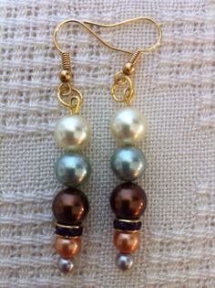 Pearl Dangle Earrings South Sea Pearls by ClearWaterDesigns by Kim Shimizu, $24.95  These Pearl Dangle Earrings have 5 South Sea Pearls in Pale Yellow,Mint Green,Brown,Dark Peach & Grey. There is an Amber Rhinestone Rondel separating the large & small Pearls.  I've used Gold Plated Ear Wire    MEASUREMENTS: 2 1/2 inches