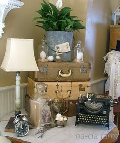 """Add stack of suitcases to the """"new"""" old typewriter & lamp, plus a plant in a graniteware bucket - old camera instead of clock?"""