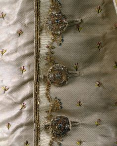 Detail waistcoat, 3-piece suit, France, ca. 1765. Saffron coloured velvet with detachable cuffs of cream silk satin, embroidered with flower sprays and exotic trees adn flowers; waistcoat: cream silk satin with matching embroidery.