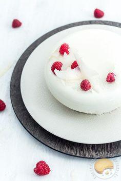 Entremet composé d'un sablé coco, d'une mousse à la crème de coco, d'un insert à la framboise le tout recouvert d'un glaçage blanc et décoré de tuiles coco